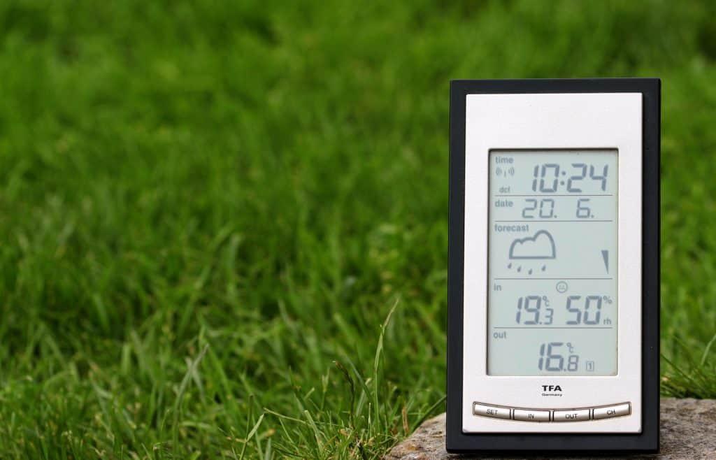 Utomhustermometer som även visar tid, datum och väderprognos. Gräsmatta i bakgrunden.