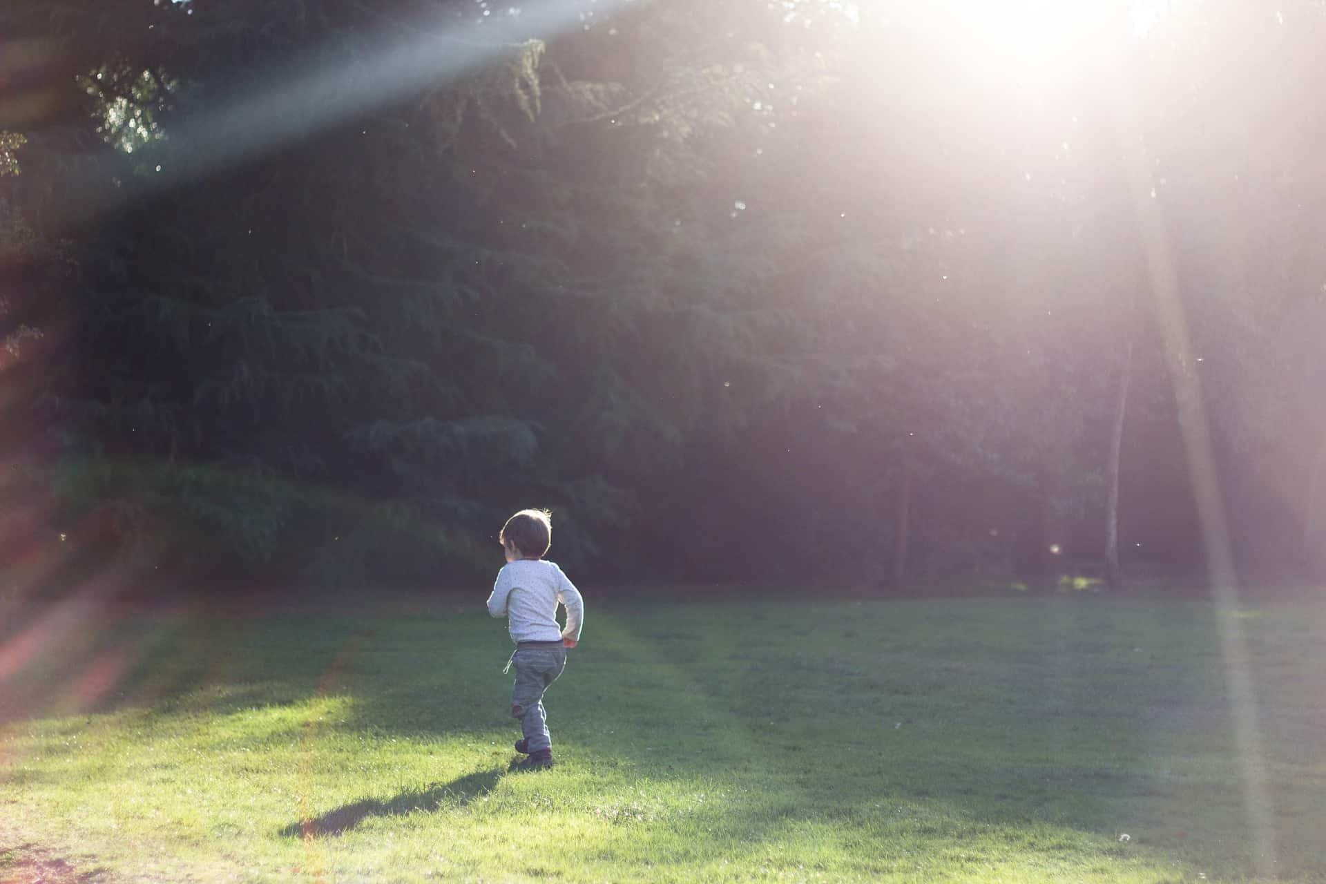 Barn springer i en solig trädgård.